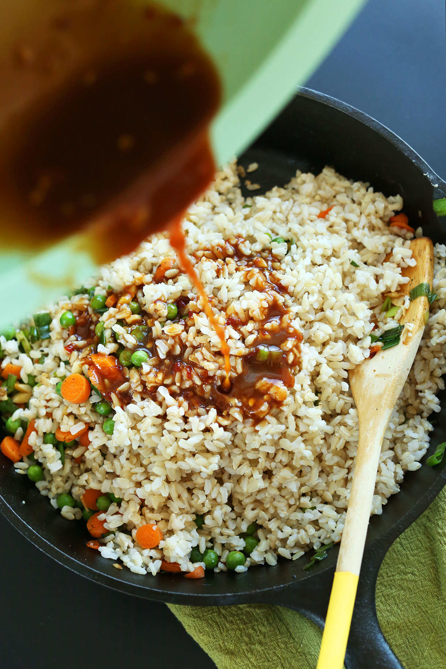 Pouring sauce into a skillet of Vegan Fried Rice with Crispy Tofu