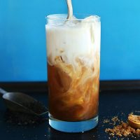 Swirling dairy-free milk into a tall glass of homemade Thai Iced Tea