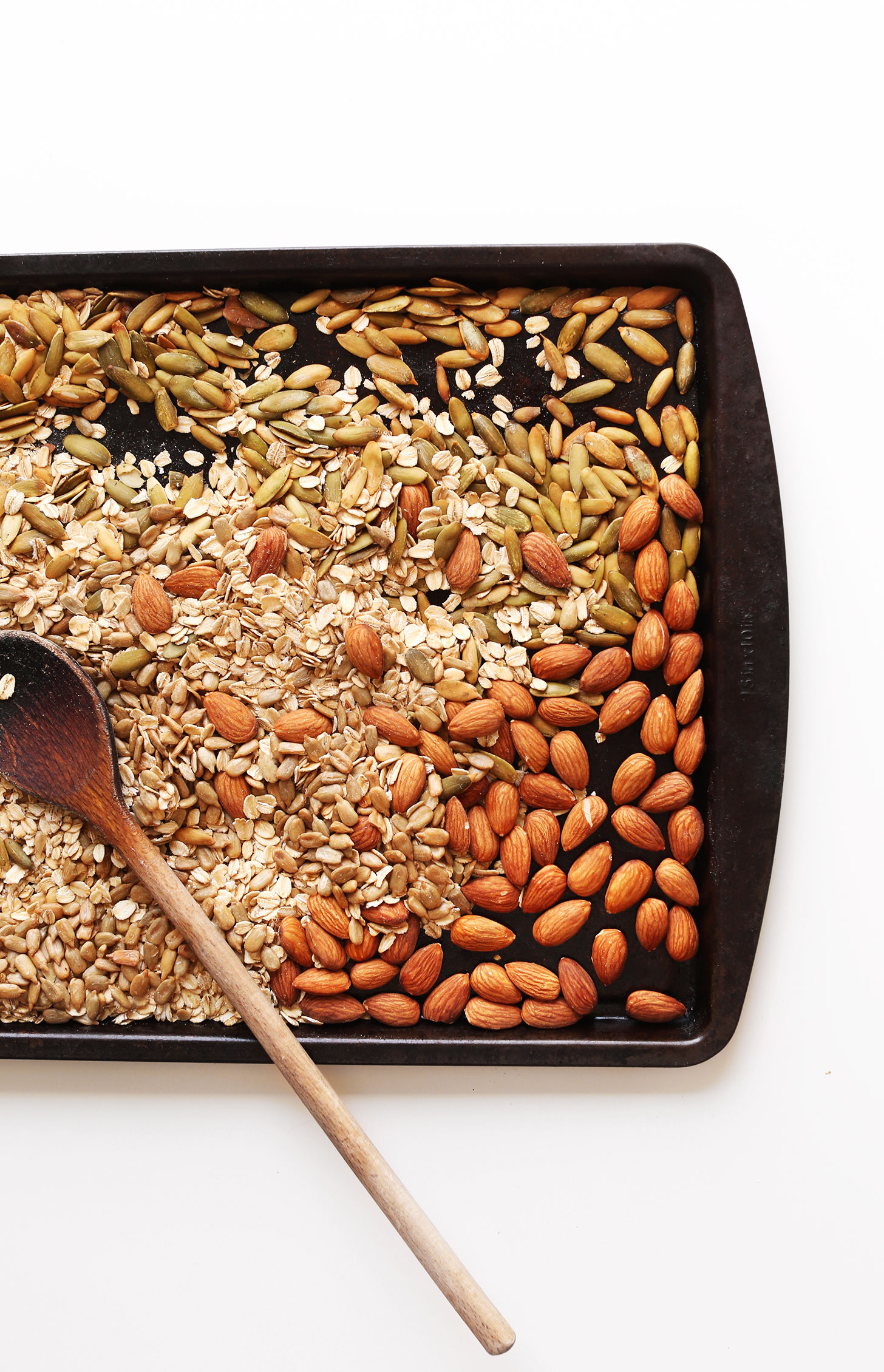 Baking sheet with nuts and seeds for making our delicious homemade muesli recipe