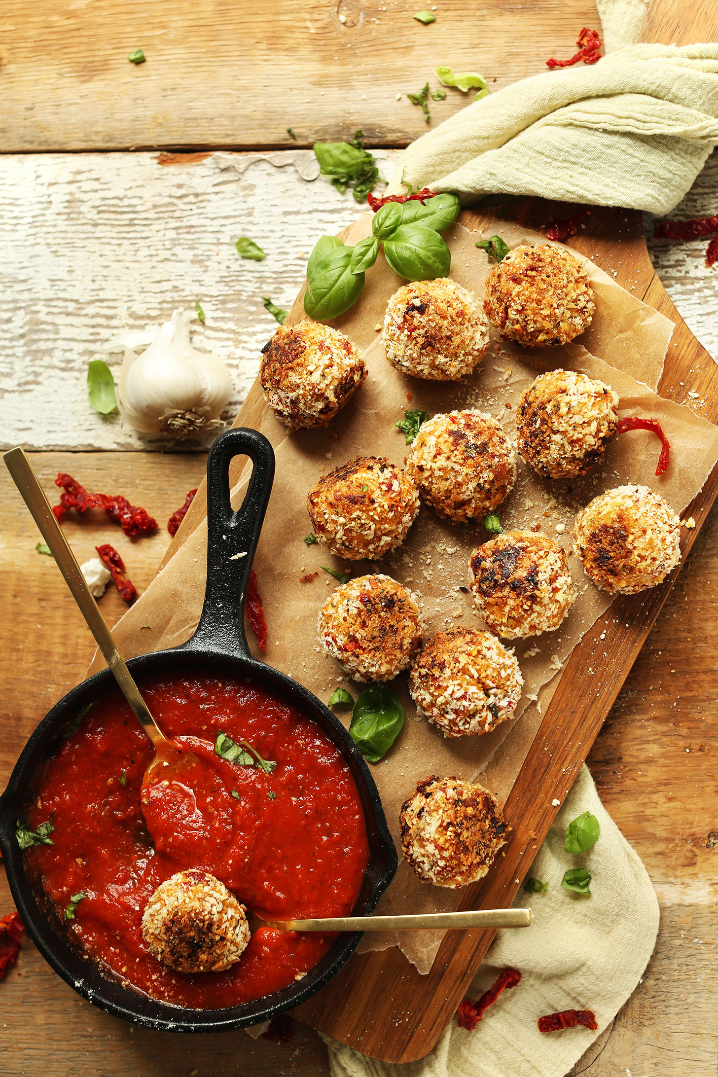 Platter of our healthy Vegan Arancini with a cast-iron skillet of warm marinara