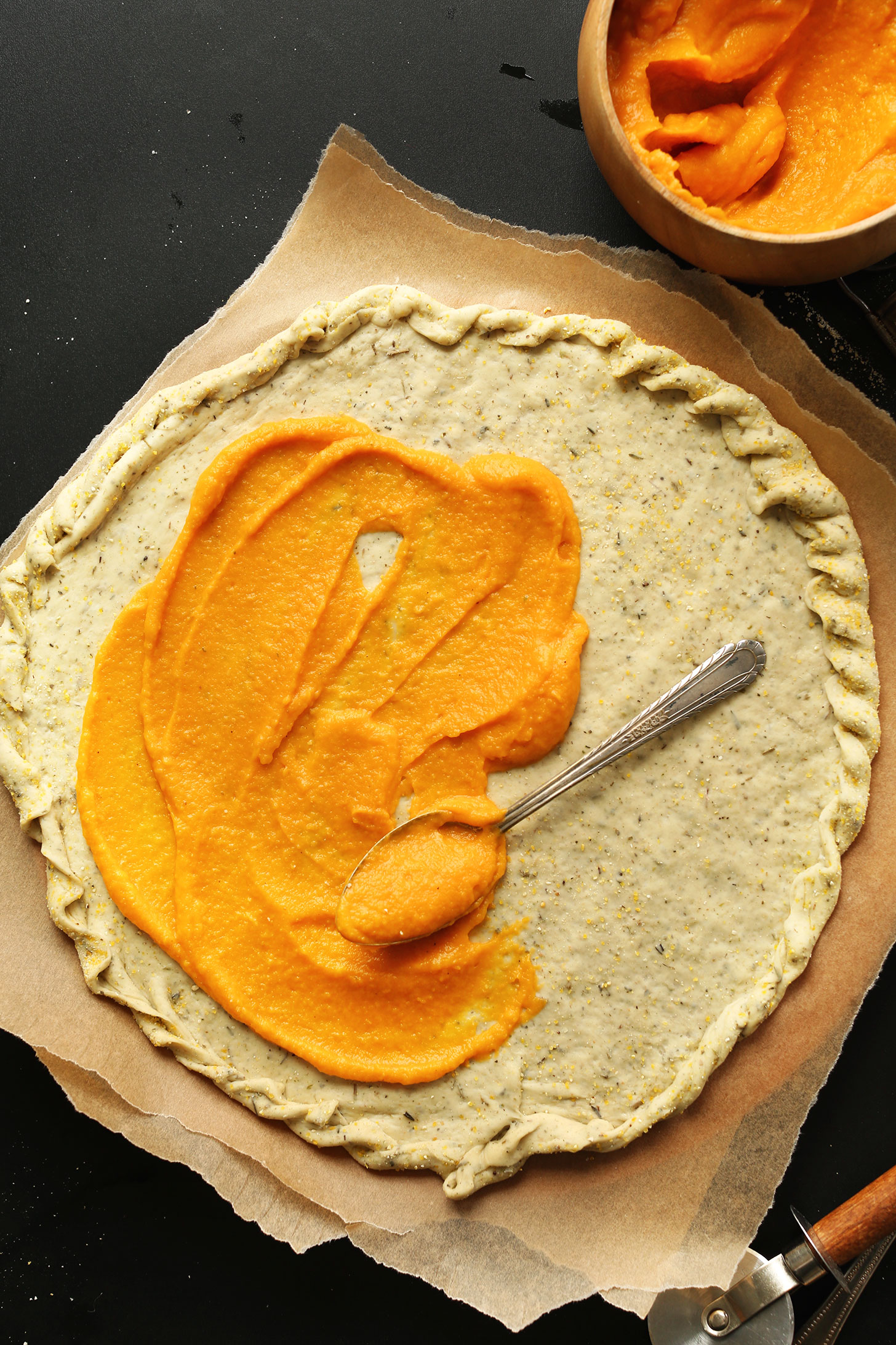 Spreading butternut squash pizza sauce onto crust for homemade vegan pizza night