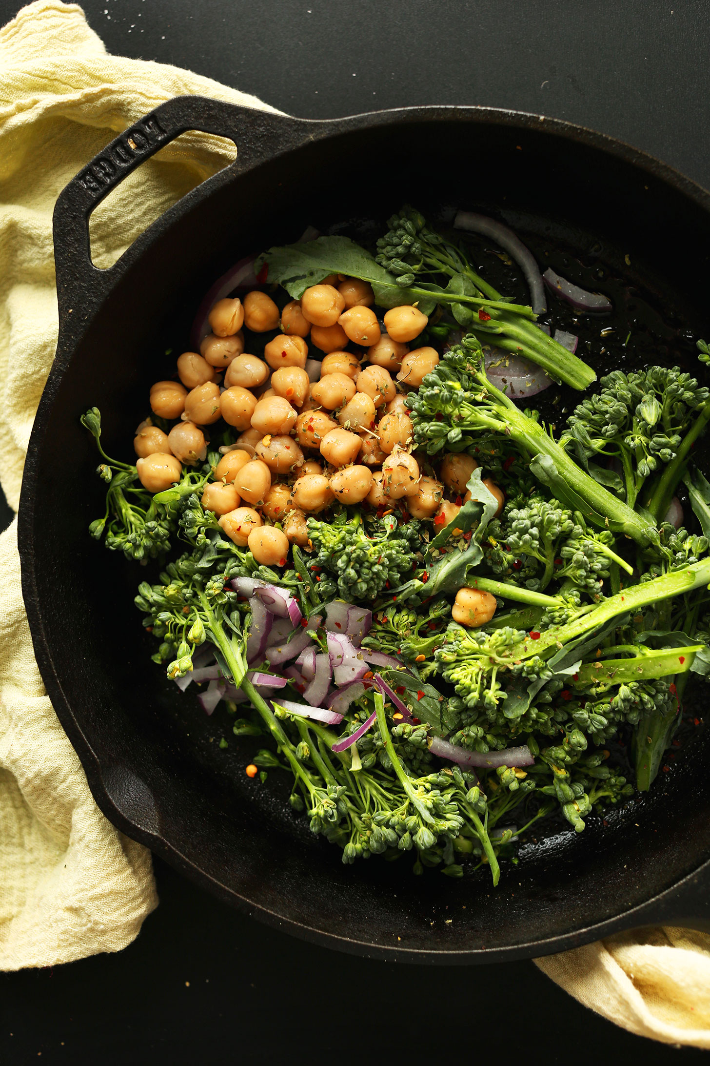 Roasting vegetables and chickpeas in a cast-iron skillet for making healthy vegan pizza