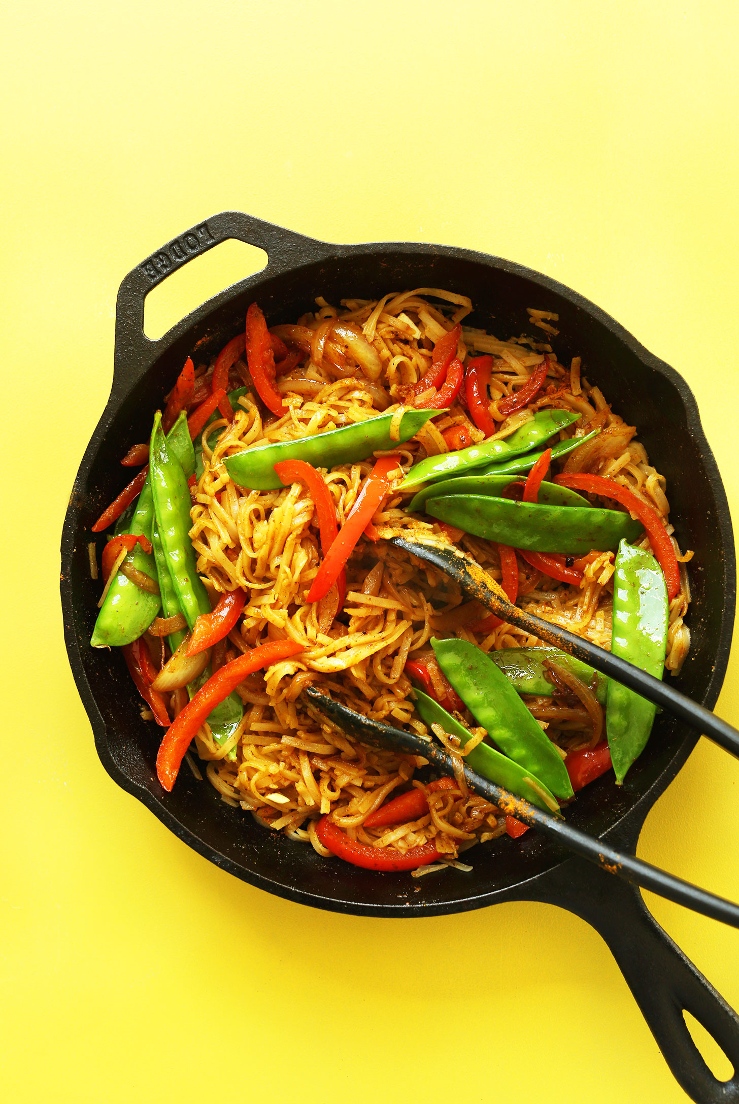 Cast-iron skillet filled with Singapore Noodles for a healthy easy vegan dinner