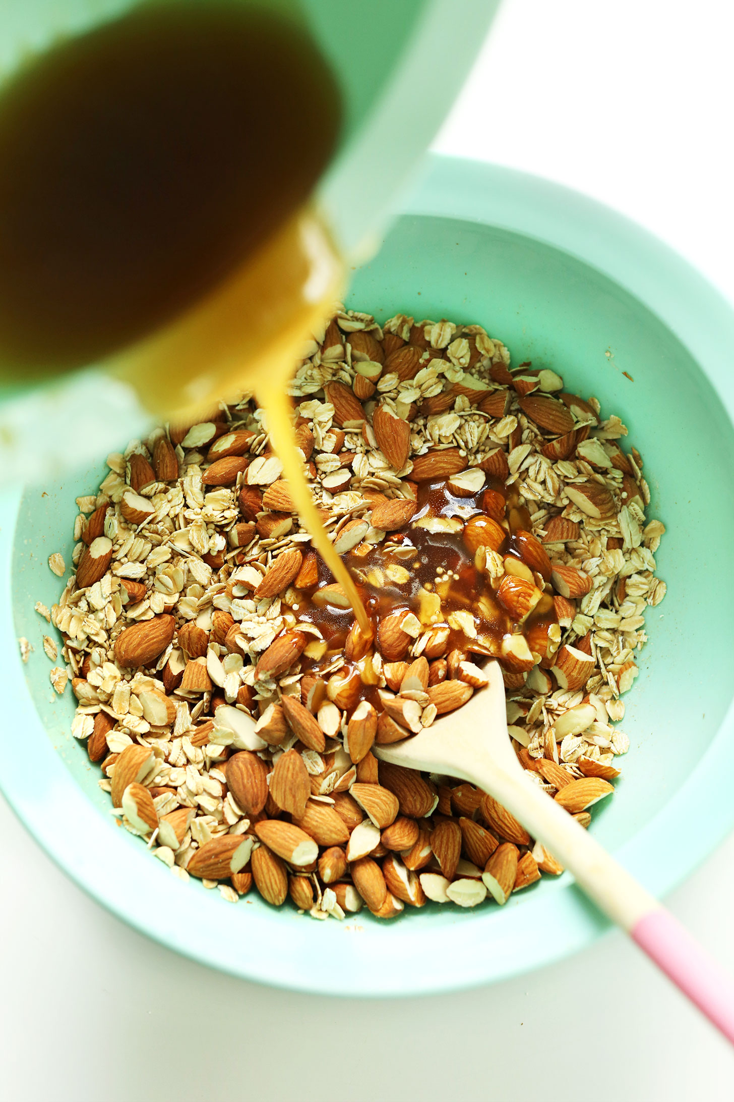 Pouring wet ingredients into dry for our homemade Quinoa Granola recipe
