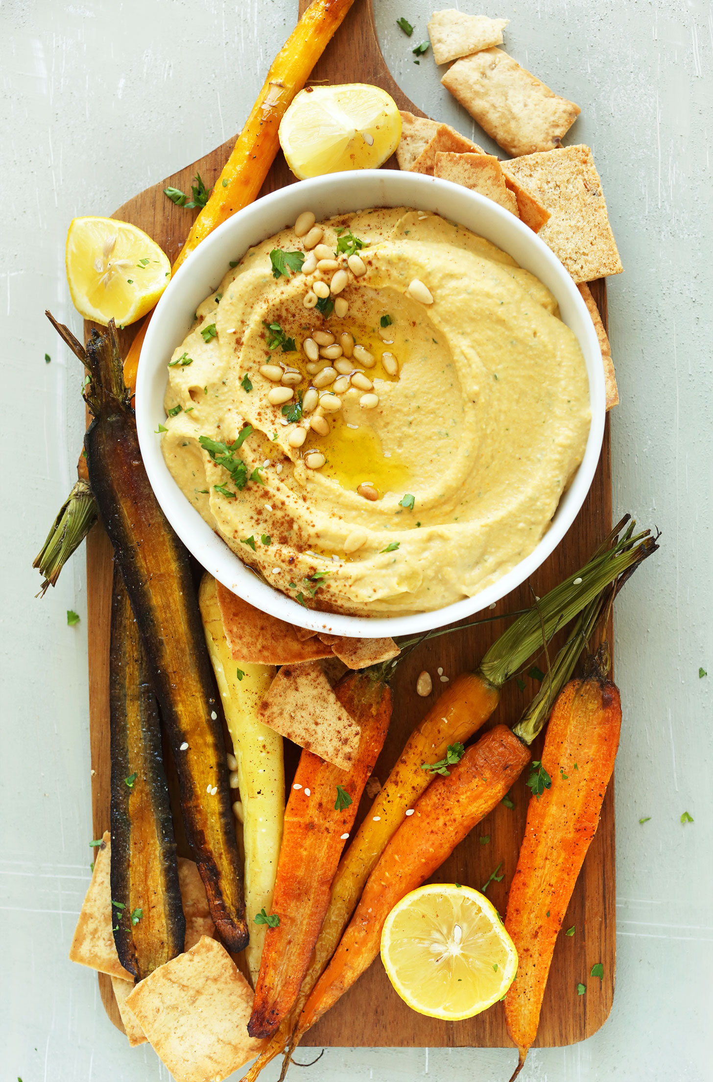 Wood platter with a bowl of gluten-free vegan Butternut Squash Hummus and goodies for dipping