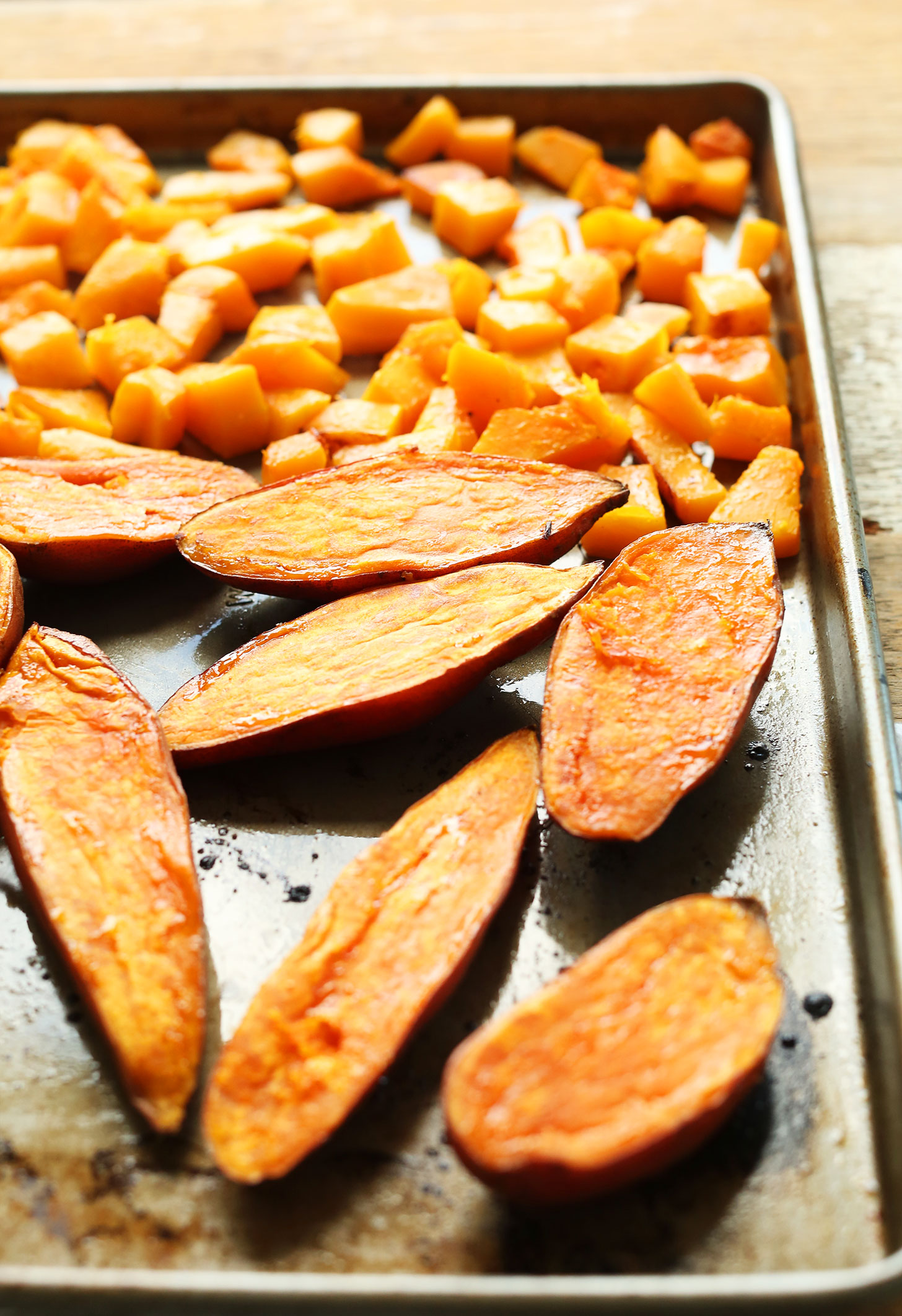 Baking sheet with sweet potatoes and butternut squash for roasting
