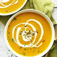 Bowls of Curried Butternut Squash Soup topped with pepitas and a coconut milk drizzle