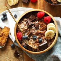 Wood bowl of our Dark Chocolate Quinoa Breakfast Bowl topped with fresh fruit
