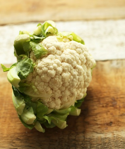 Head of cauliflower on a wood cutting board