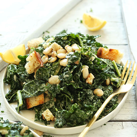 Gold fork resting on a plate of Vegan White Bean Kale Salad