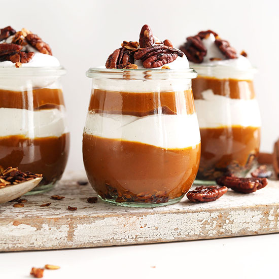 Three small jars of our Pumpkin Pie Parfaits recipe with orange and white layers