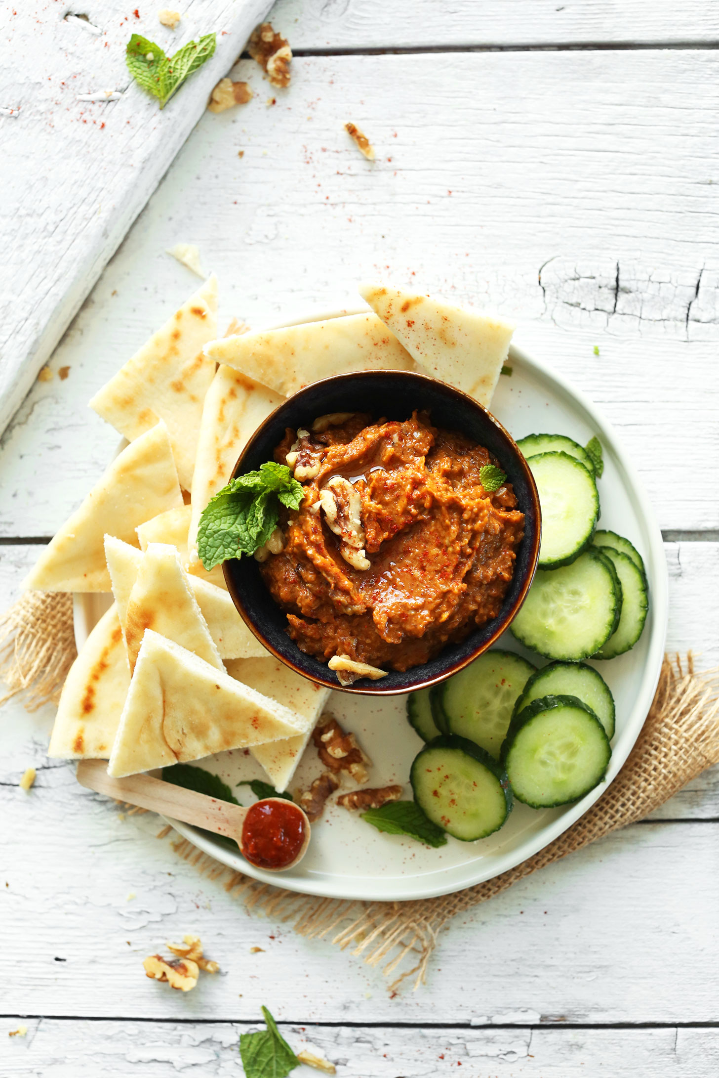 Bowl of our Smoky Harissa Eggplant Dip recipe surrounded by sliced cucumbers and pita bread for dipping