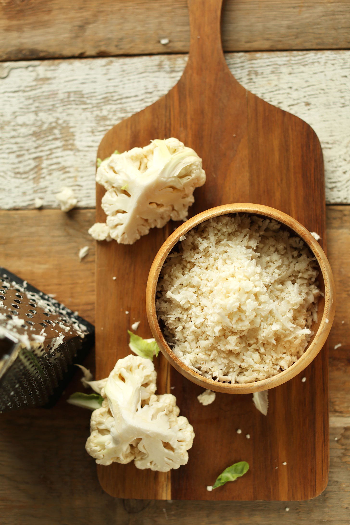 Bowl of cauliflower rice, a grater, and pieces of chopped cauliflower ready to be grated