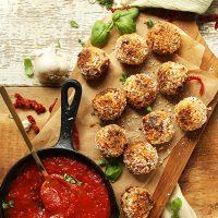 Skillet of marinara sauce beside a batch of Sun-Dried Tomato & Basil Arancini