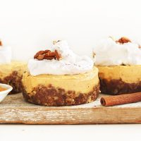 Wood board with three Vegan Pumpkin Cheesecakes topped with coconut whip and pecans