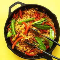 Tongs in a skillet of Vegan Singapore Noodles made with snow peas