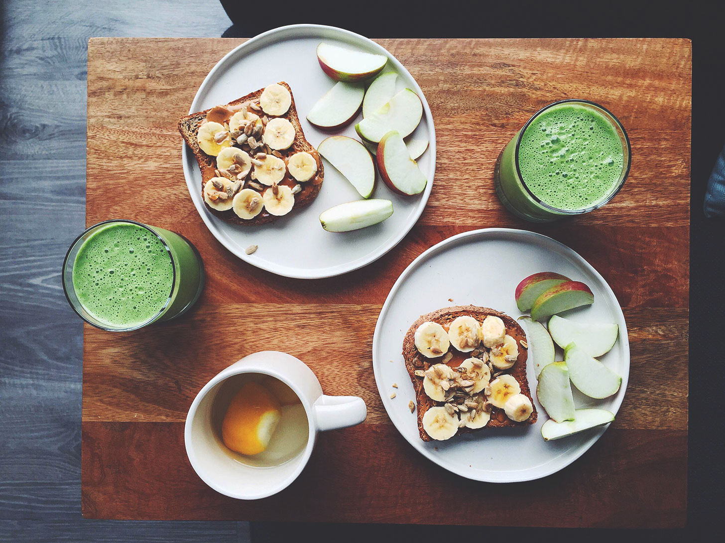 Photo showing green smoothies, nut butter toast, and sliced apples for breakfast