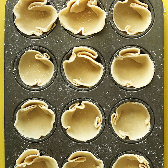 Mini muffin tin filled with Coconut Oil Pie Crust ready to be baked
