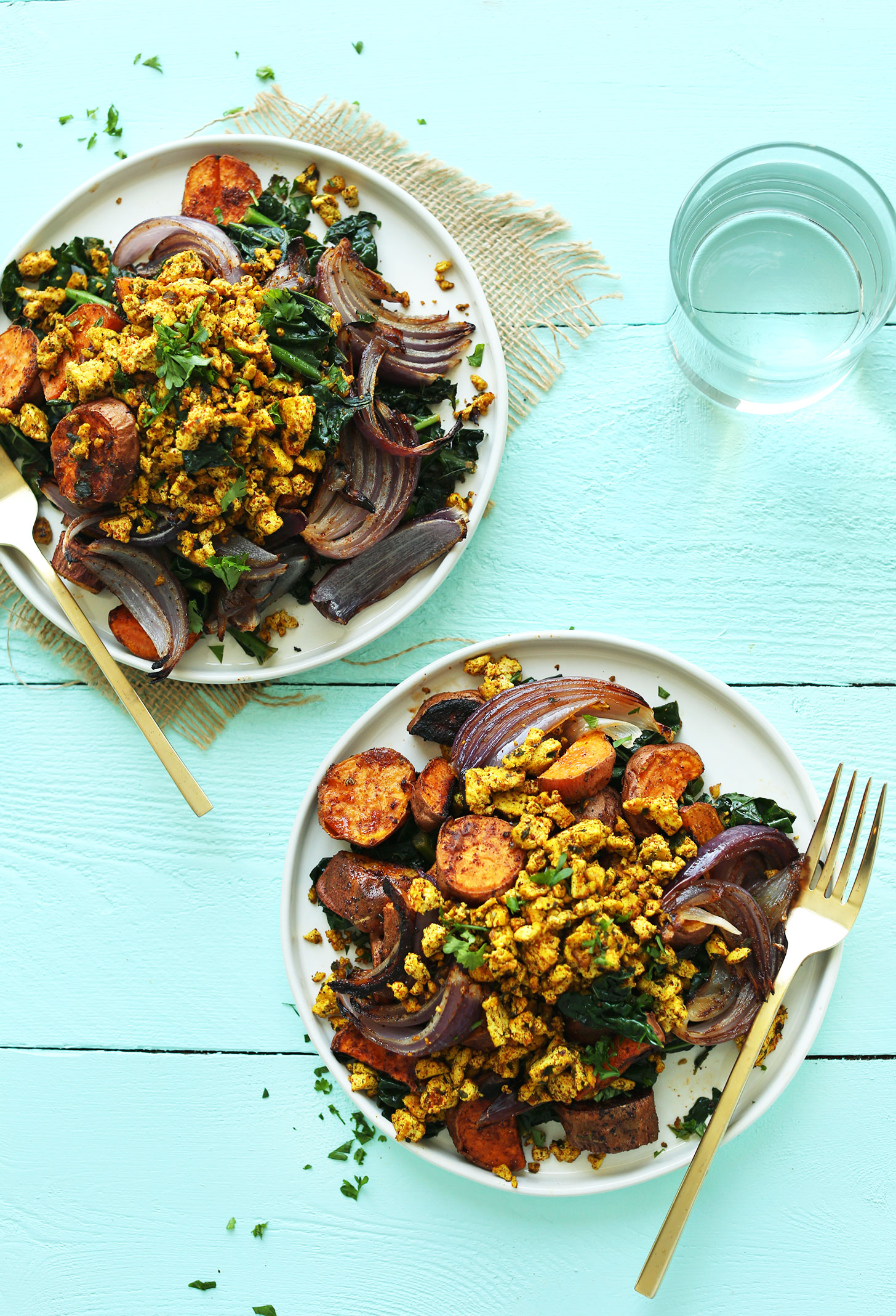 Two plates of our super healthy vegan breakfast of Savory Tofu Scramble with Kale, Sweet Potatoes, and Roasted Red Onion