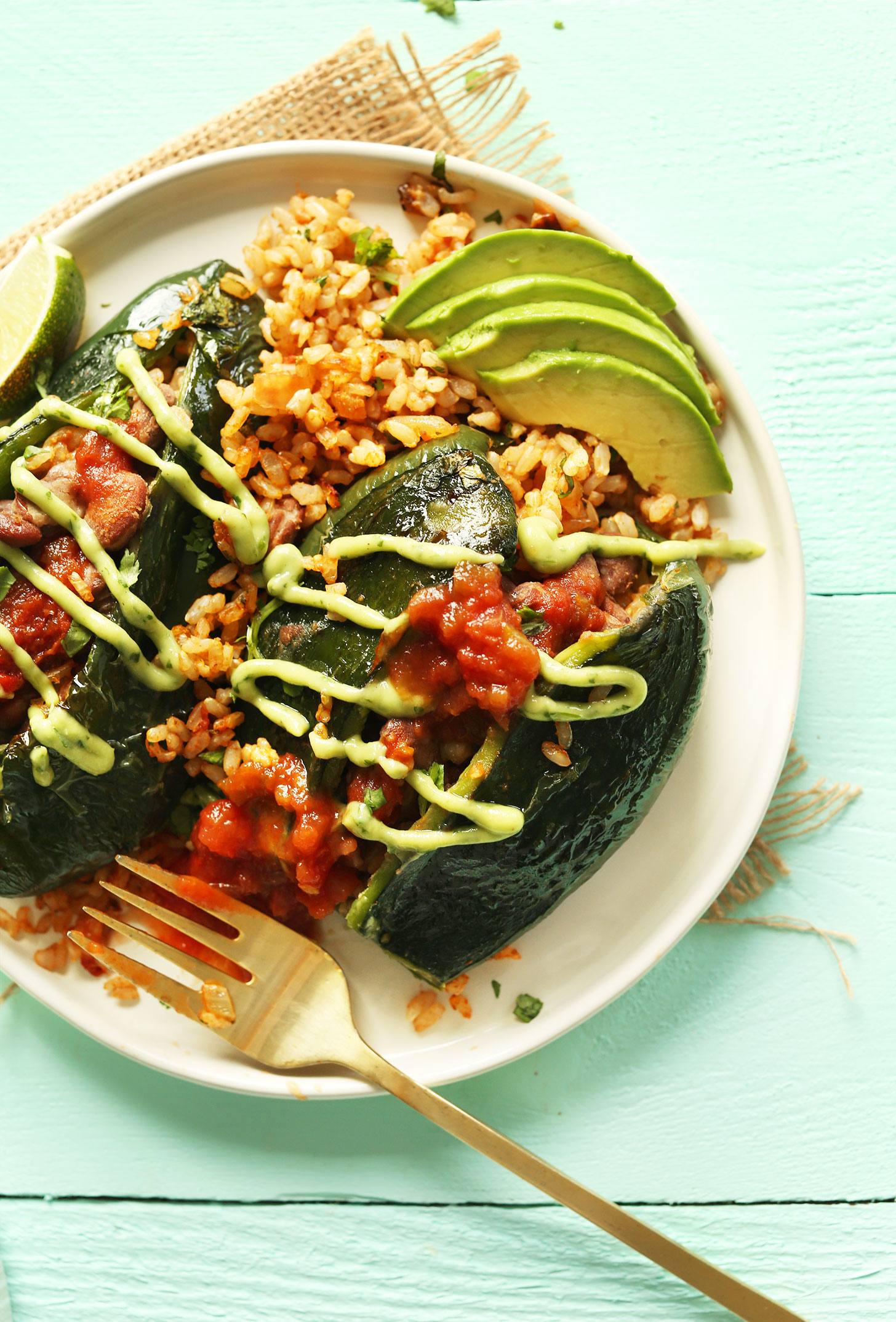 A plate of Vegan Mexican Stuffed Poblano Peppers drizzled with creamy avocado cilantro dressing