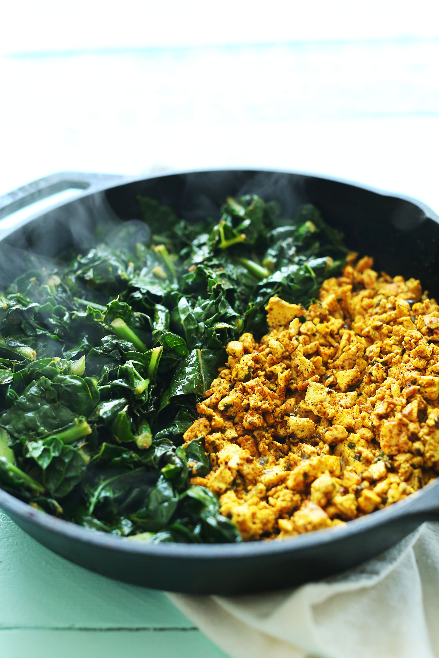 Cooking kale and tofu in a cast-iron skillet for our Savory Tofu Scramble recipe