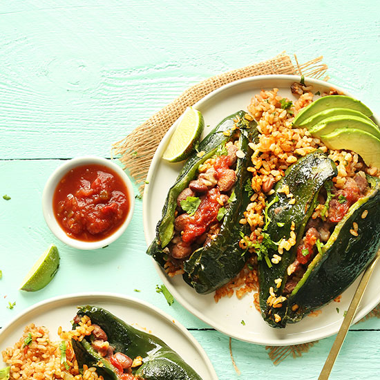 Plate of Stuffed Poblano Peppers with rice and sliced avocado