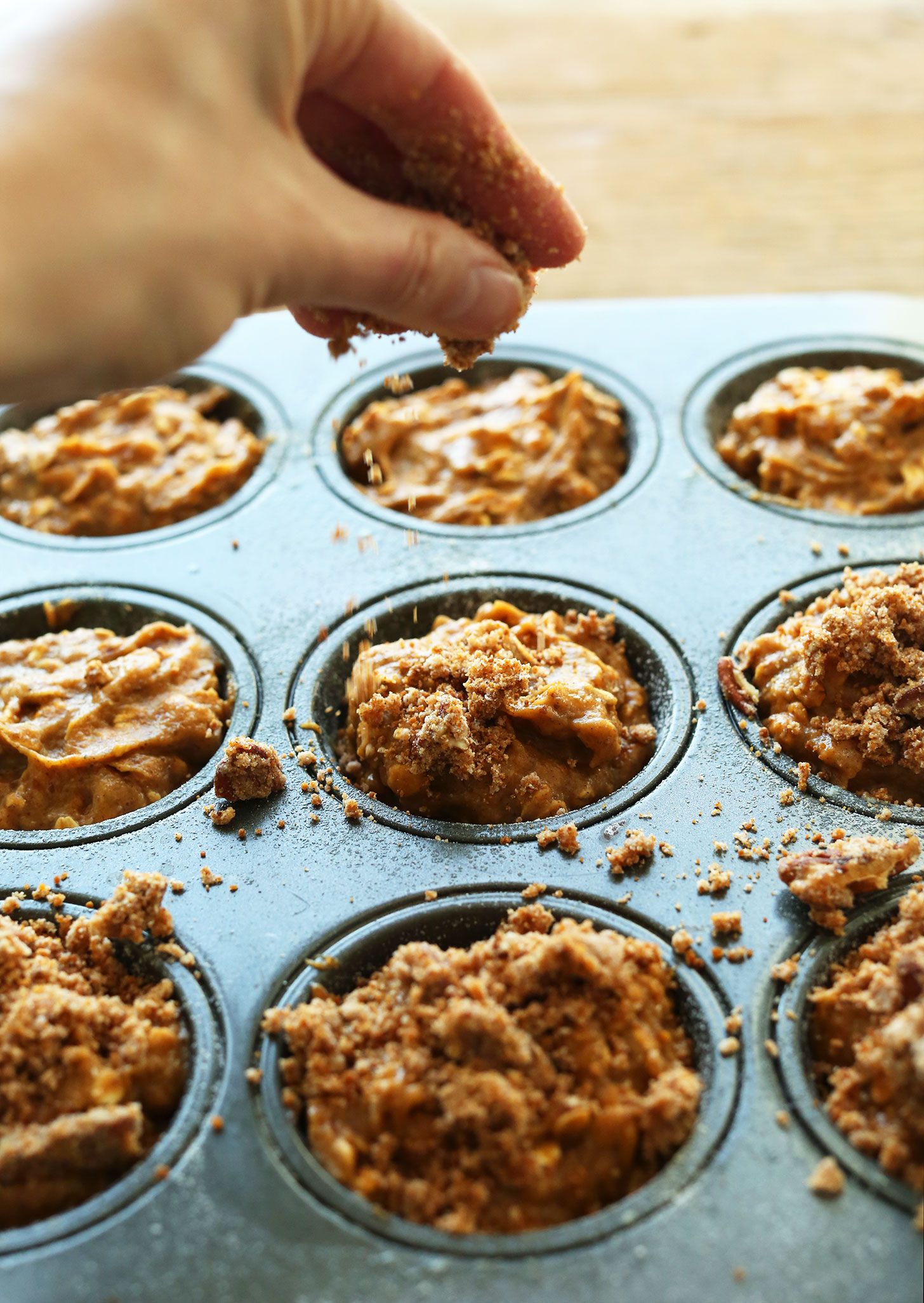 Sprinkling delicious Pecan Crumble Topping over gluten-free vegan Pumpkin Spices Muffins