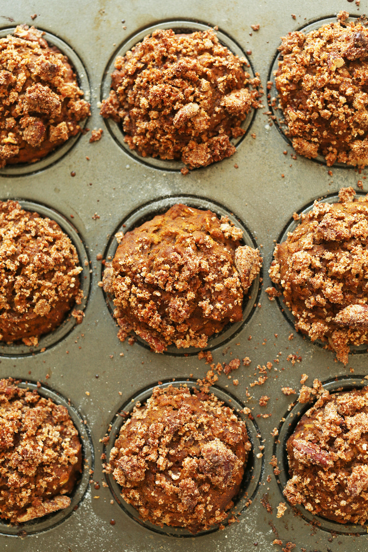 Muffin tin filled with freshly baked Vegan Pumpkin Spice Muffins with a Pecan Crumble Topping