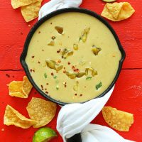 Skillet filled with Vegan Green Chili Queso surrounded by tortilla chips