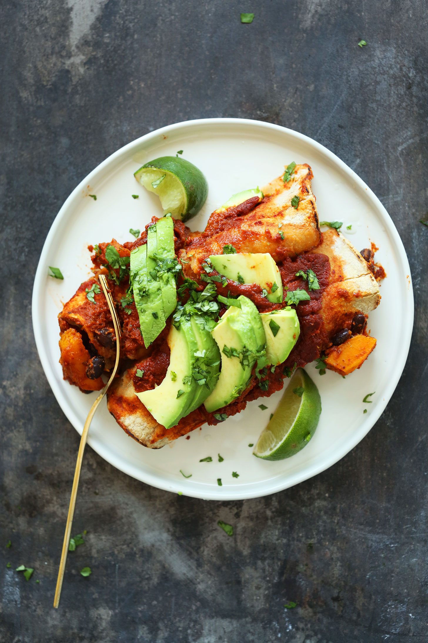 Plate with two Butternut Squash Enchiladas topped with avocado slices