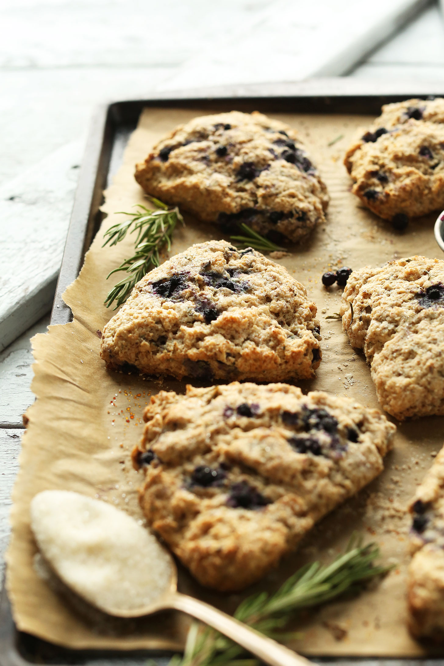 Parchment-lined baking sheet with Rosemary Blueberry Scones for a delicious vegan breakfast