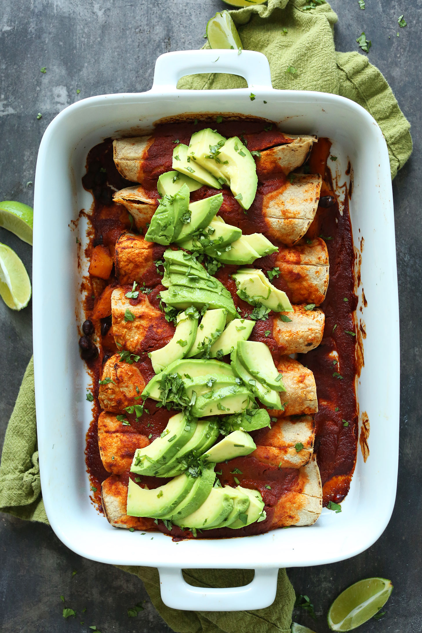 Ceramic dish filled with Butternut Squash Enchiladas topped with avocado