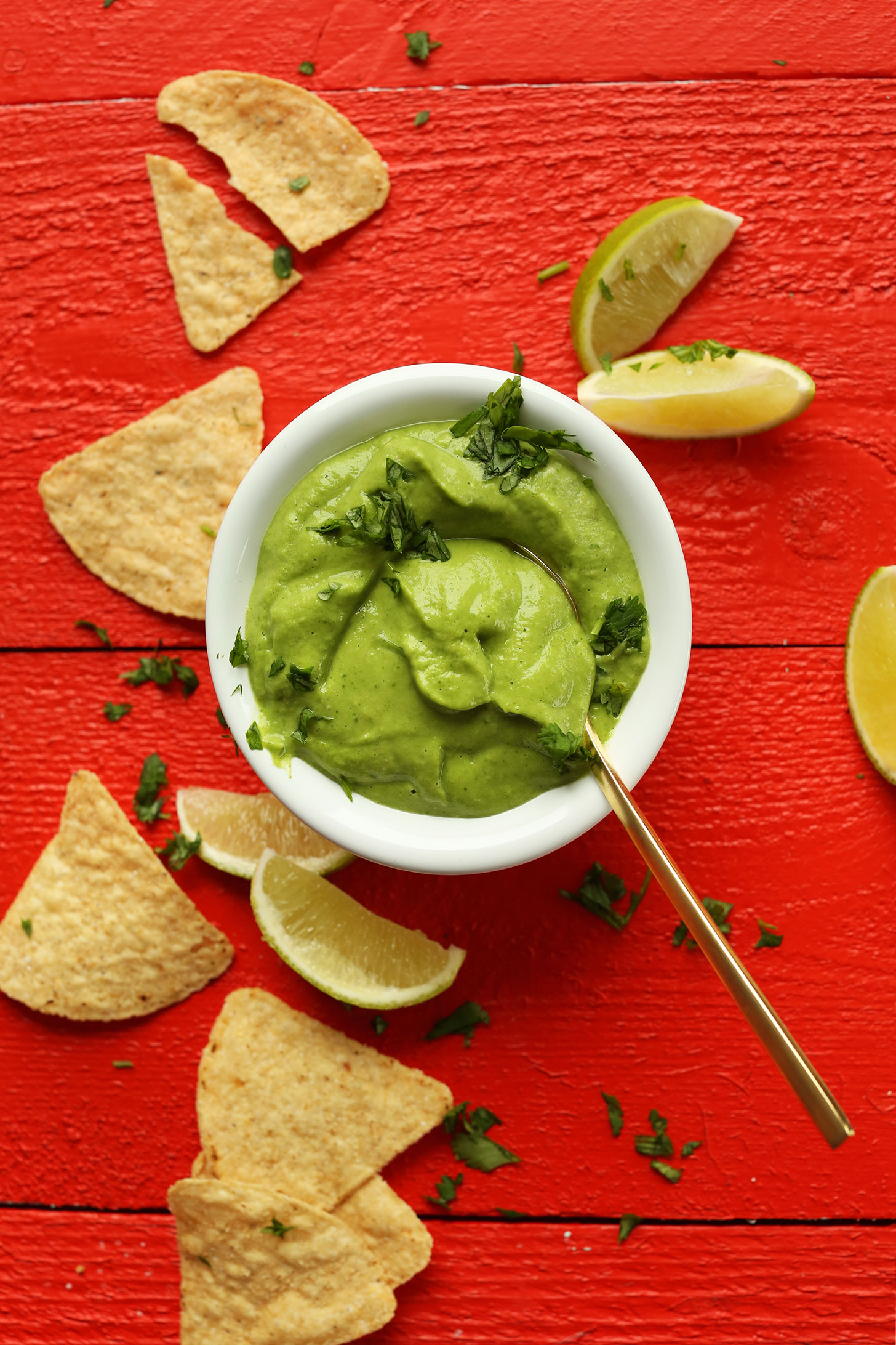 Bowl of our creamy avocado cilantro dressing surrounded by tortilla chips and limes
