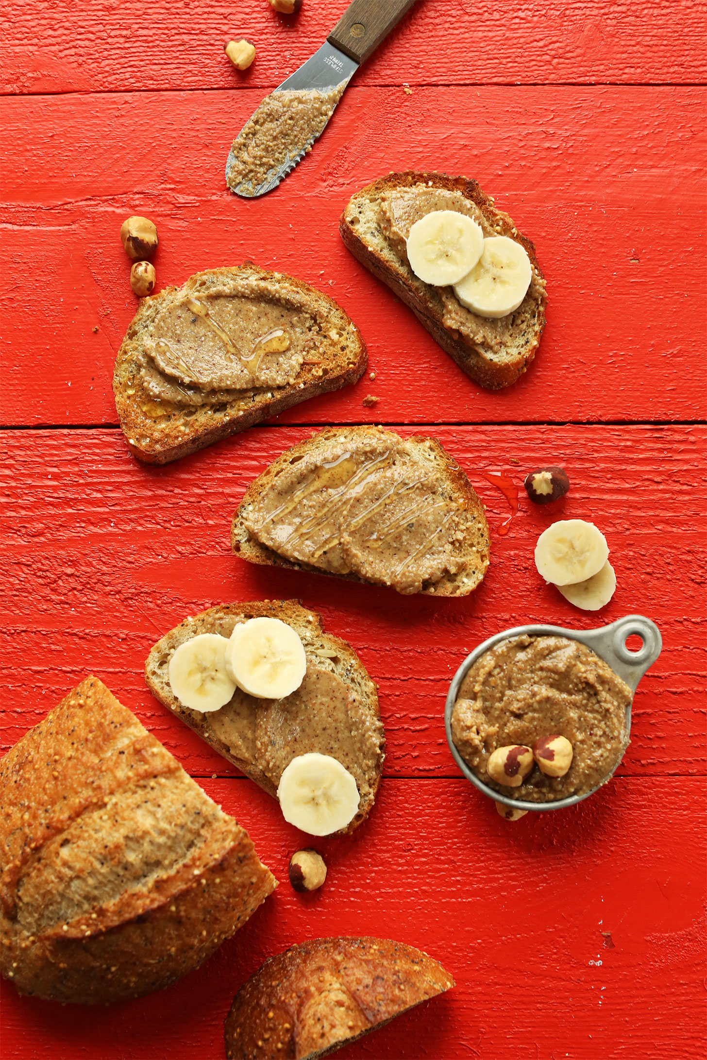 Sliced gluten-free bread topped with creamy homemade hazelnuts butter, honey, and peanut butter