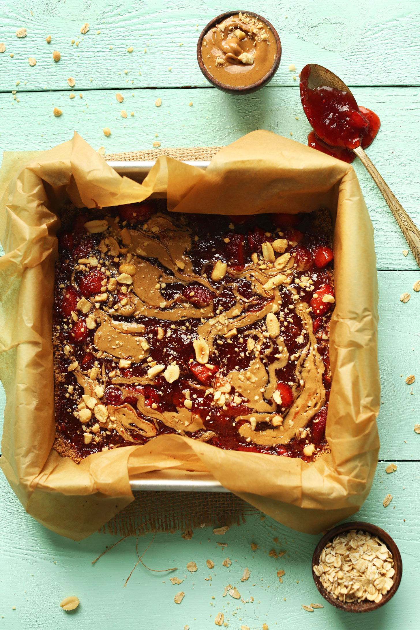 Parchment-lined baking pan filled with a batch of our PB&J Bars recipe for a gluten-free vegan snack
