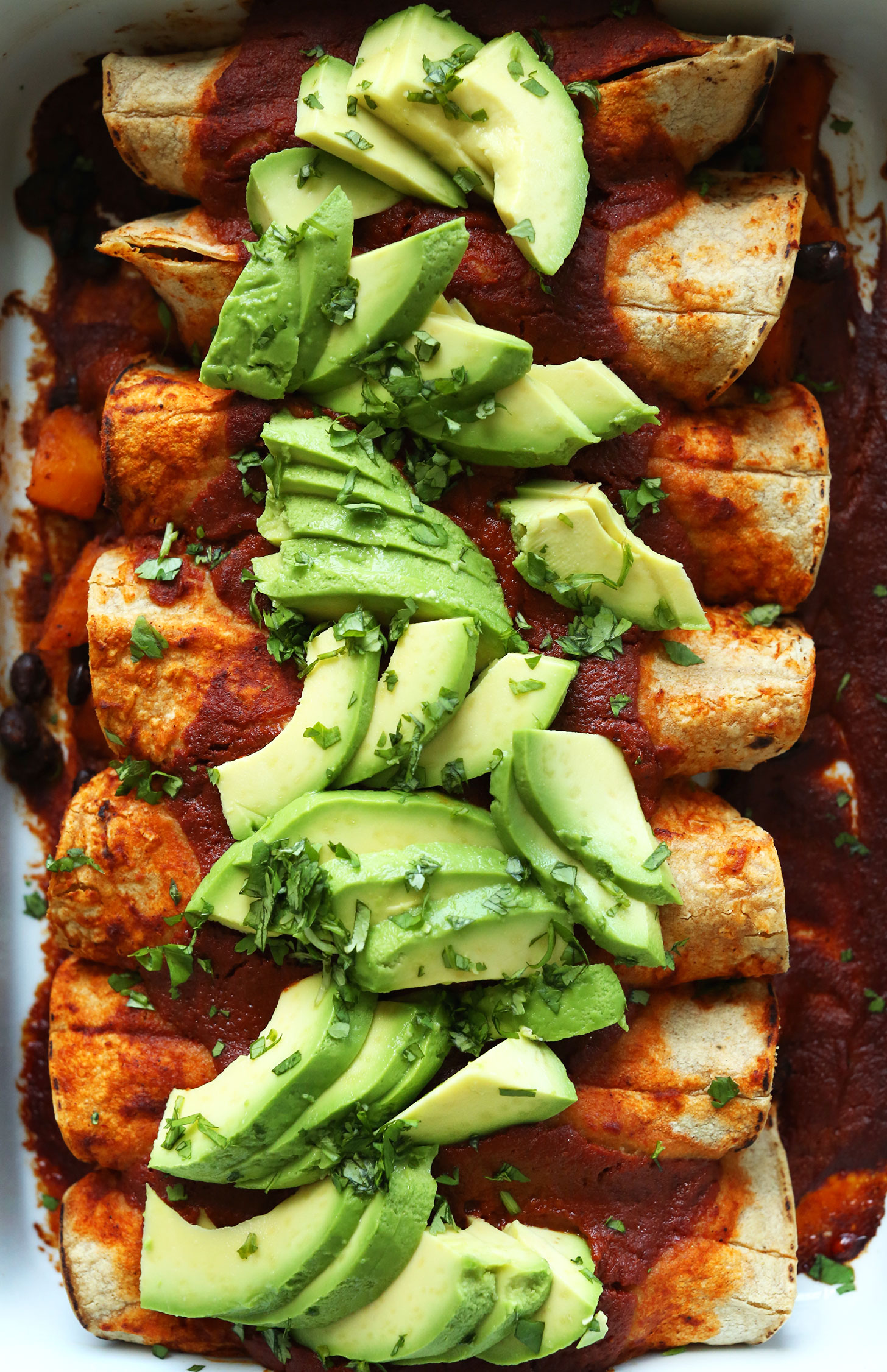 Dish filled with Butternut Squash Enchiladas topped with freshly sliced avocadoes