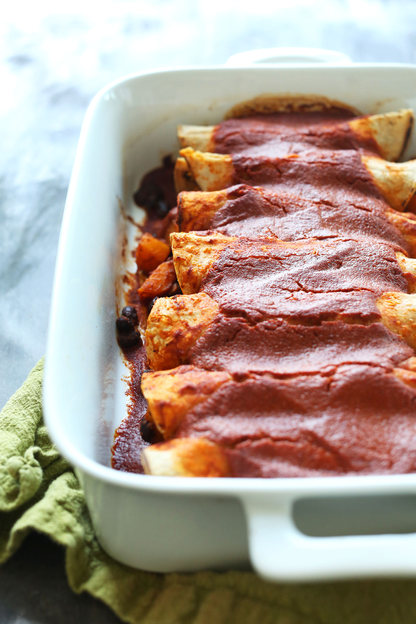 Ceramic baking dish filled with Butternut Squash Enchiladas for a gluten-free plant-based dinner
