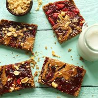 Peanut Butter and Jelly Snack Bars beside dairy-free milk and a bowl of peanuts