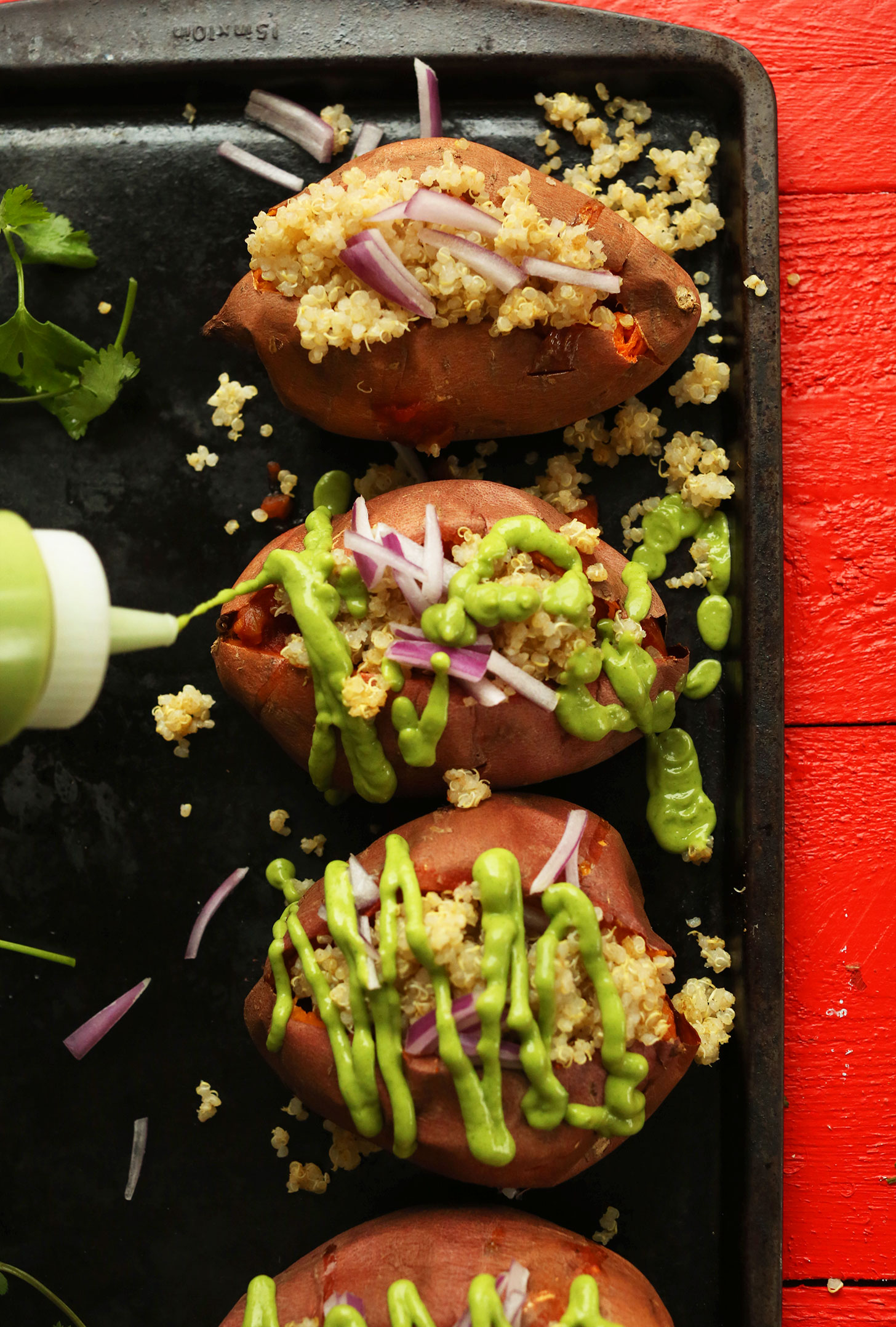 Drizzling avocado cilantro sauce over a tray of Quinoa Stuffed Sweet Potatoes