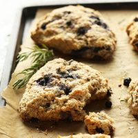 Parchment-lined baking sheet with homemade Rosemary Blueberry Scones and fresh rosemary sprigs