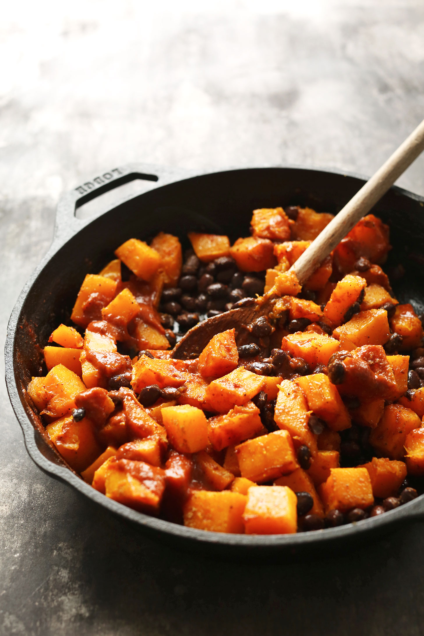 Stirring butternut squash and black beans with enchilada sauce in a cast-iron skillet