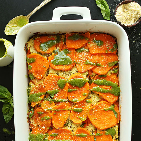 Baking pan filled with homemade Sweet Potato Lasagna drizzled with basil pesto