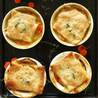 Four ramekins of White Bean & Thyme Mini Vegan Pot Pies on a baking sheet