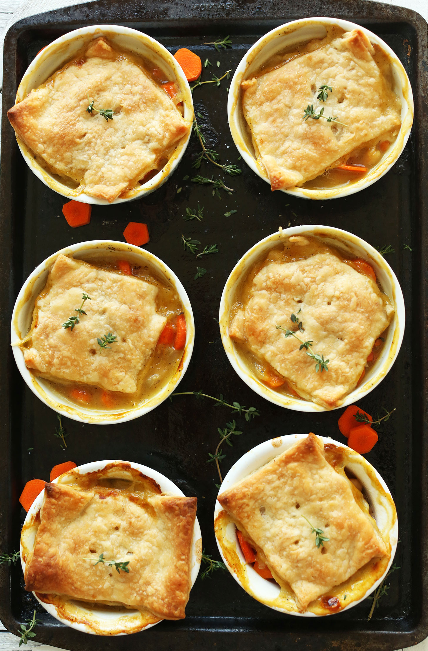 Baking sheet with six ramekins filled with White Bean & Thyme Vegan Pot Pies