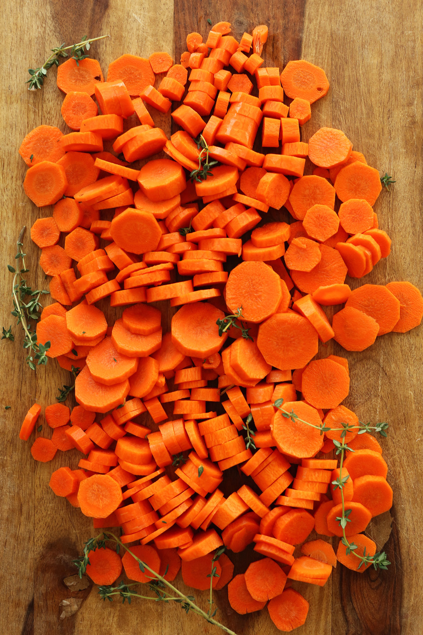 Peeled and sliced carrots surrounded by sprigs of fresh thyme