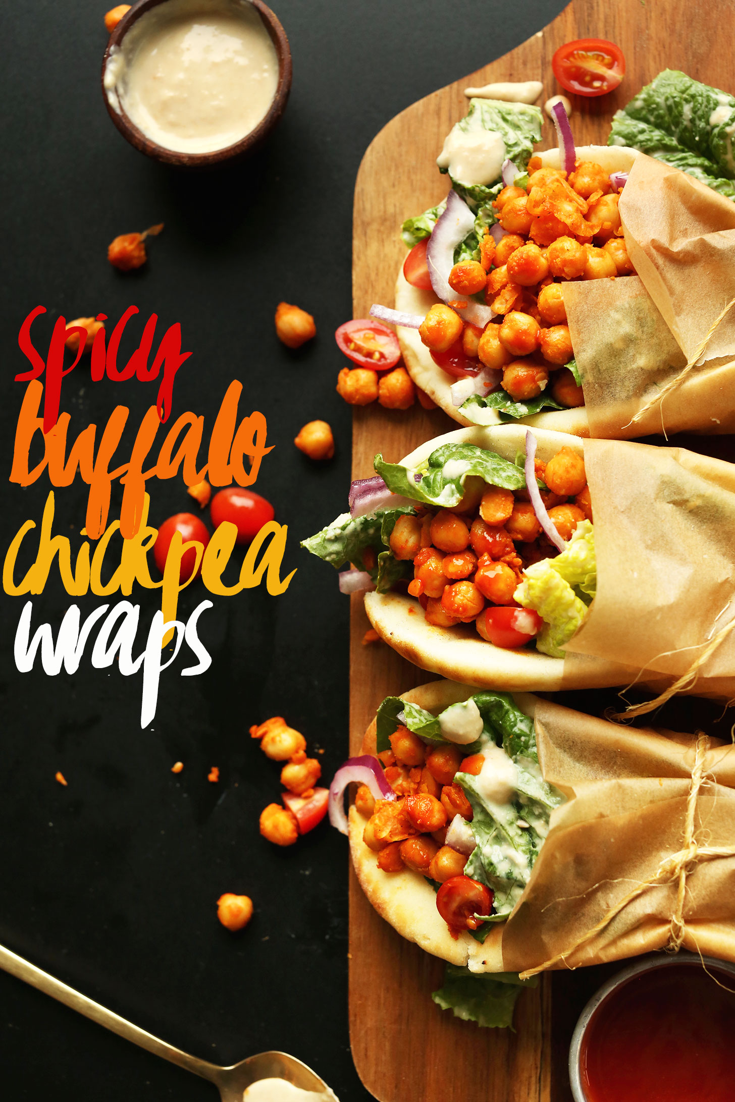 Rolled up vegan Buffalo Chickpea Wraps served on soft pita bread