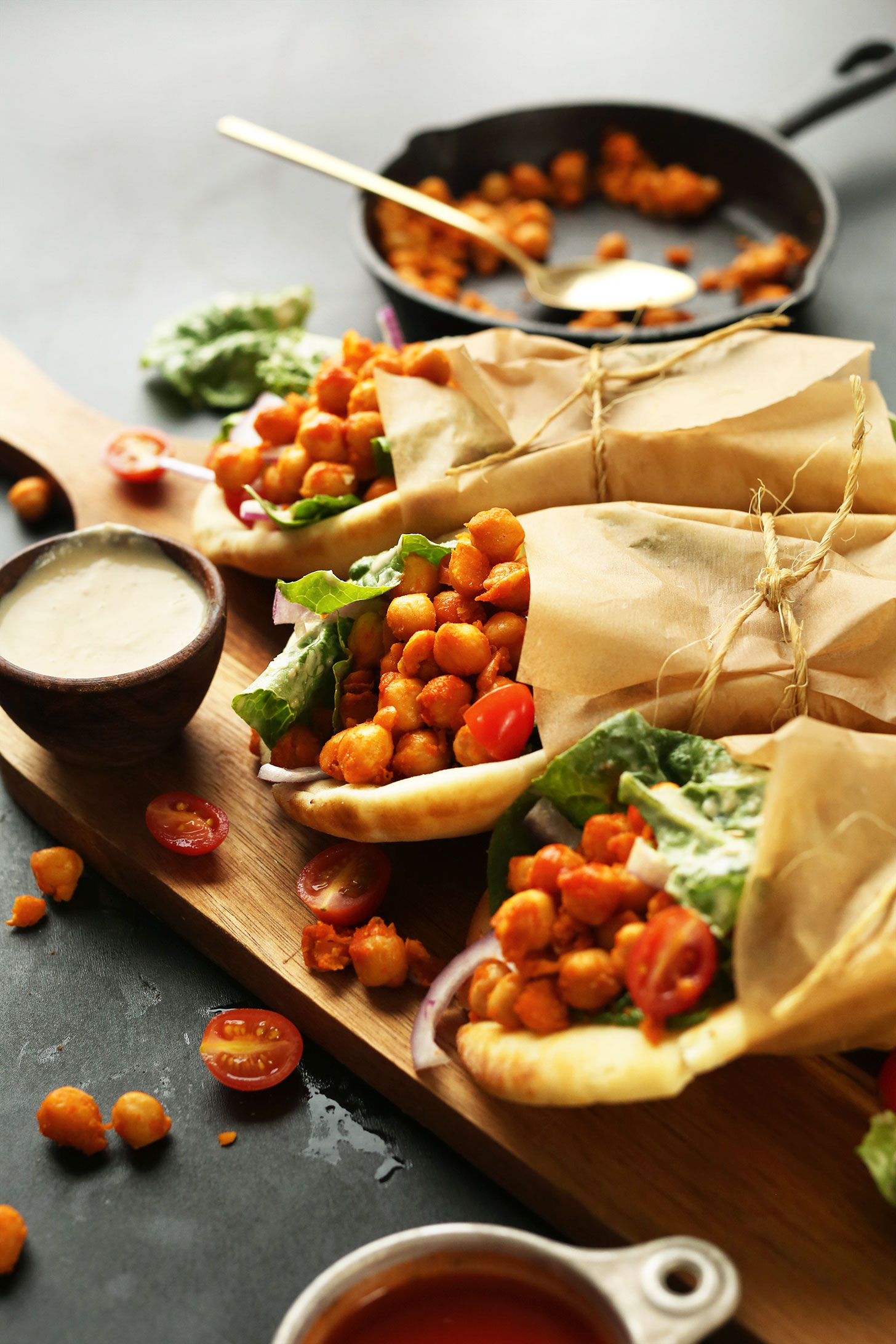 Rolled vegan Buffalo Chickpea Wraps with a side of creamy hummus dressing