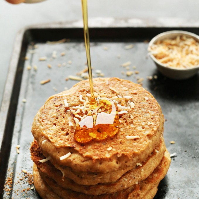 Pouring maple syrup onto a stack of delicious Vegan Toasted Coconut Pancakes