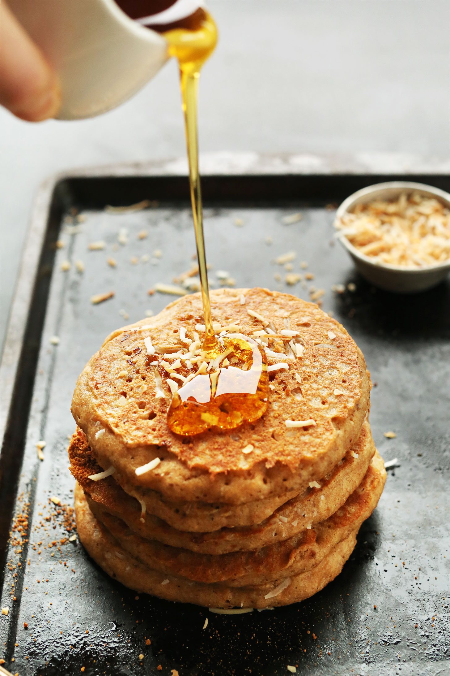 Drizzling maple syrup onto a stack of Vegan Toasted Coconut Pancakes