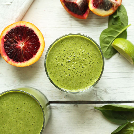 Two glasses filled with our Blood Orange Green Smoothie recipe alongside ingredients used to make it
